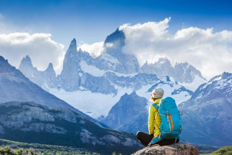 Woman on top of mountains, staring into distance.